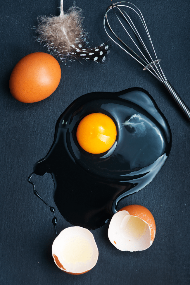 Two eggs, one cracked open, with a whisk and a feather on a black background